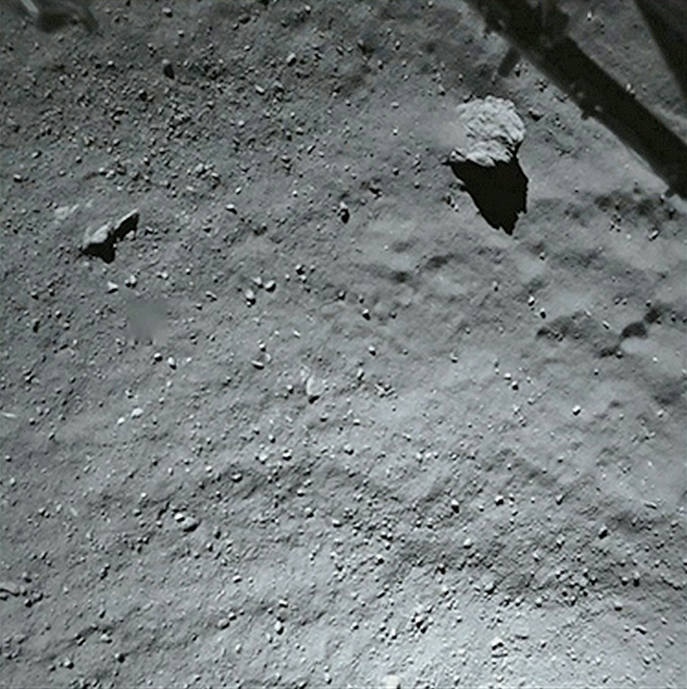 Image du site du 1er contact de Philae avec la surface de la comète 67P prise juste avant l'atterrissage par la caméra de ROLIS le 12 novembre 2014, à près de 40 m d'altitude. Le bloc en haut mesure 5 m de diamètre. Crédits : ESA/Rosetta/Phila...